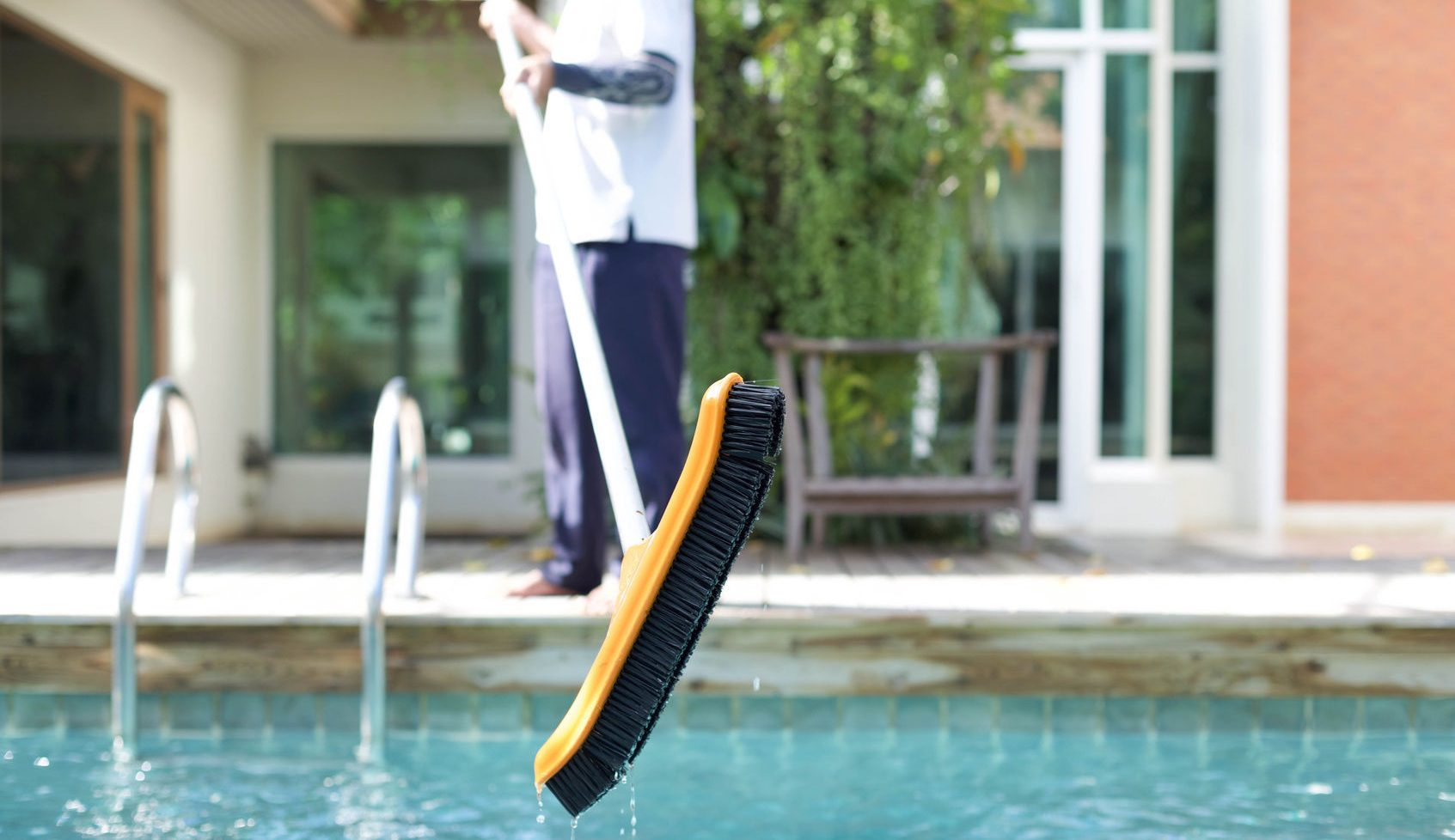 cleaning a swimming pool with a brush in summer time